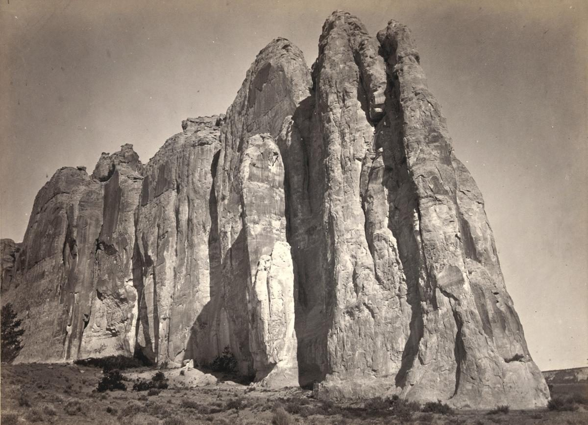 The south side of Inscription Rock (renamed El Morro National Monument), in New Mexico - 1873. Note the small figure of a man standing at bottom center. The prominent feature stands near a small pool of water, and has been a resting place for travelers for centuries. Since at least the 17th century, natives, Europeans, and later American pioneers carved names and messages into the rock face as they paused. In 1906, a law was passed, prohibiting further carving
