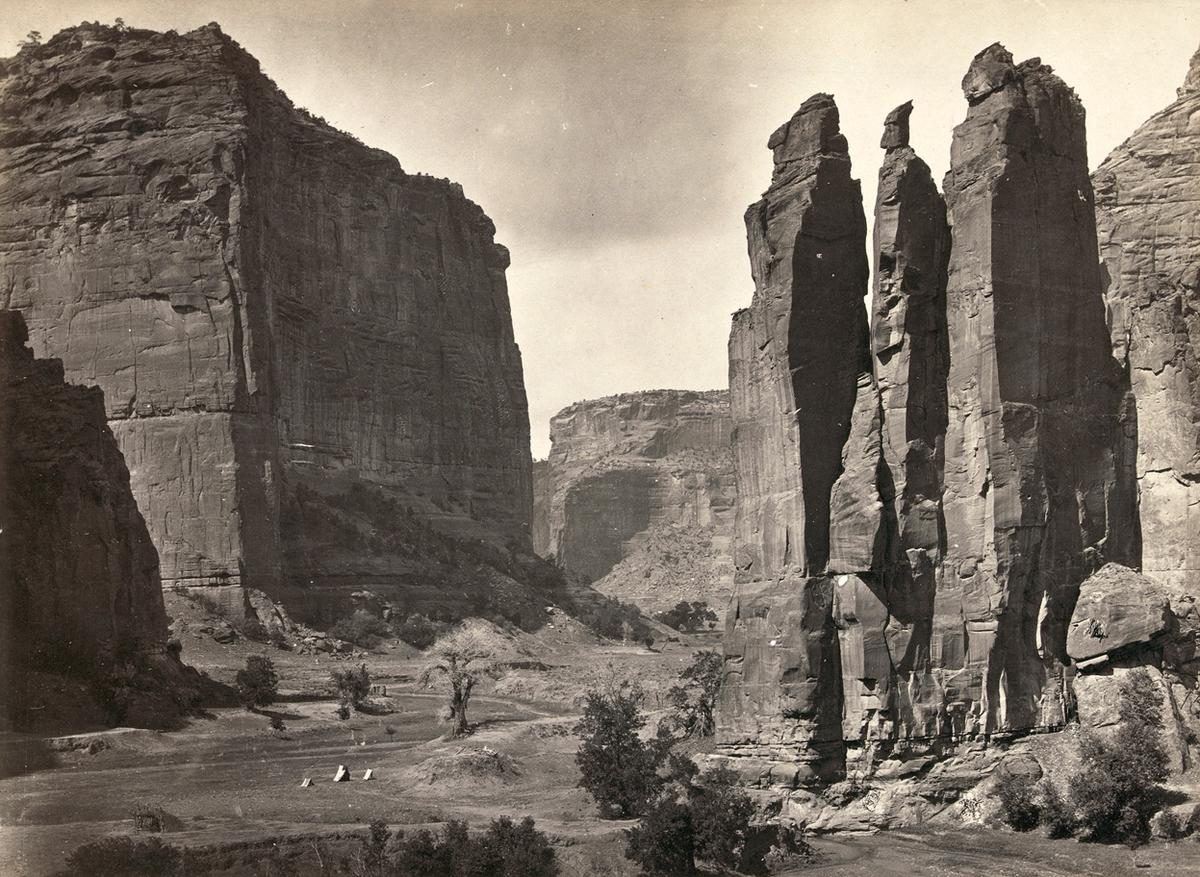 "Panoramic view of tents and a camp identified as ""Camp Beauty"", rock towers and canyon walls in Canyon de Chelly National Monument, Arizona. Tents and possibly a lean-to shelter stand on the canyon floor, near trees and talus. Photographed in 1873"