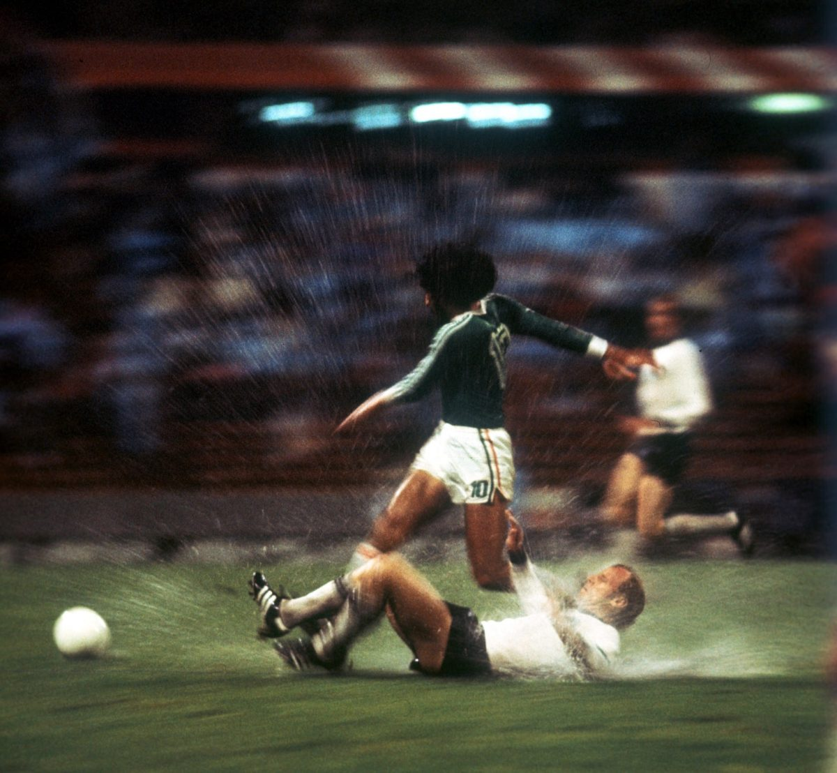 Berti Vogts of West Germany takes a bath tackling a Mexican opponent at the 1978 World Cup finals