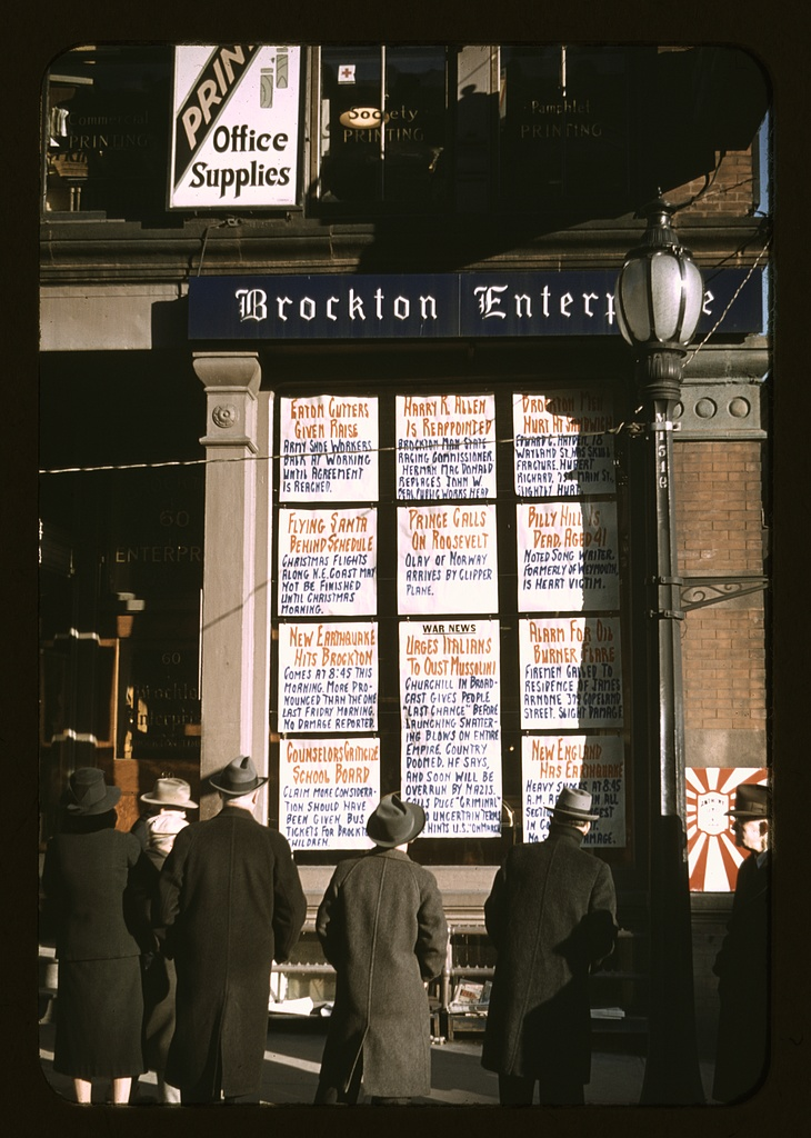 Jack DElano Men and a woman reading headlines posted in street-corner window of Brockton Enterprise newspaper office on Christmas Eve, Brockton, Mass. Dec 24 1940