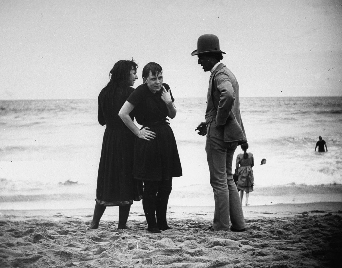 Aug. 24, 1886 An actor talks with bathers on the beach.
