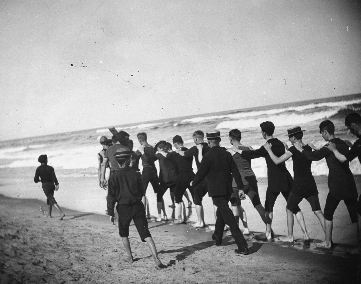 Aug. 23, 1886 A group of young male bathers walk single file along the beach.