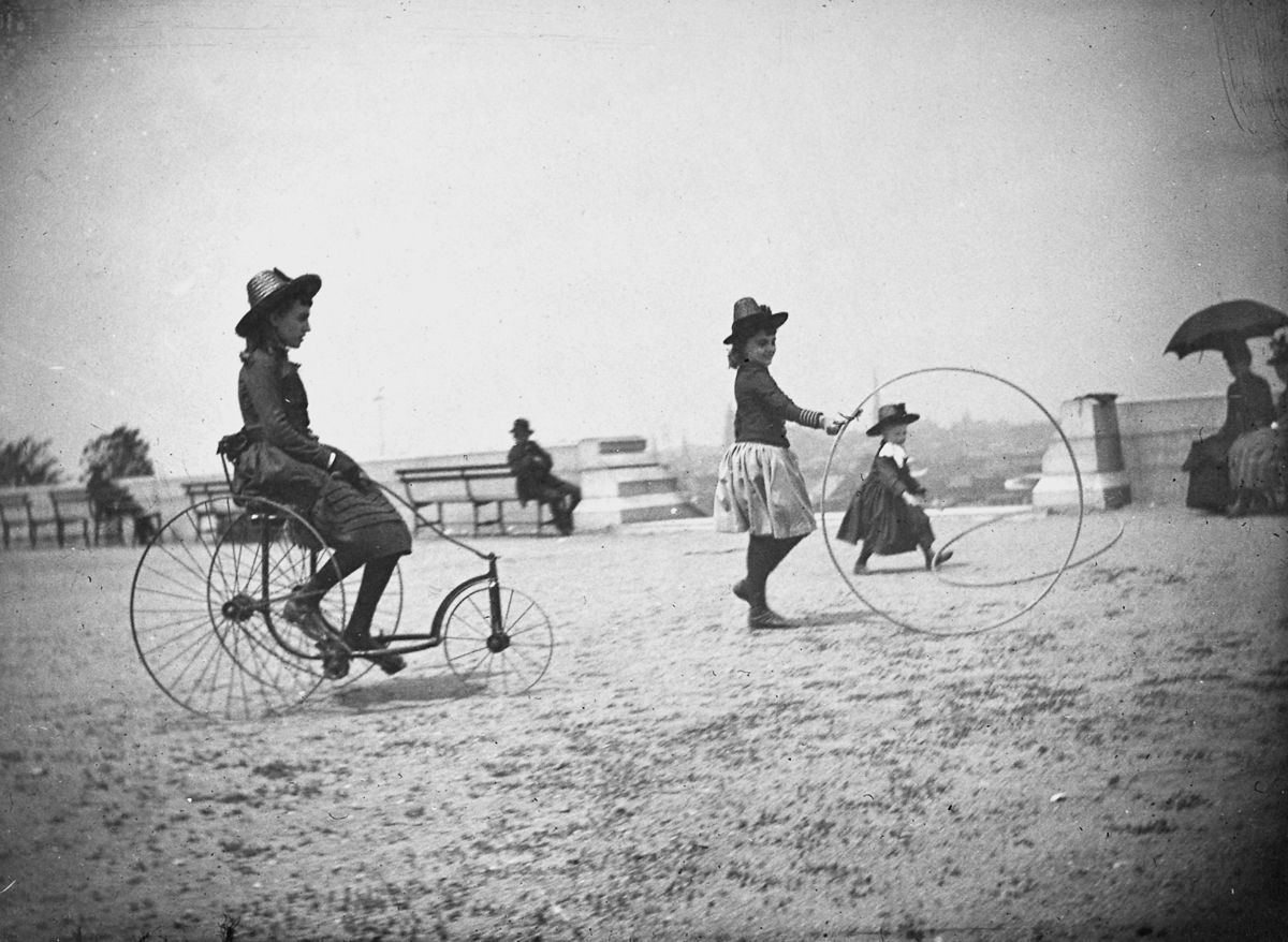 May 22, 1886 Isabel Harter rides a tricycle while her sister Nellie rolls a hoop in Fort Greene.