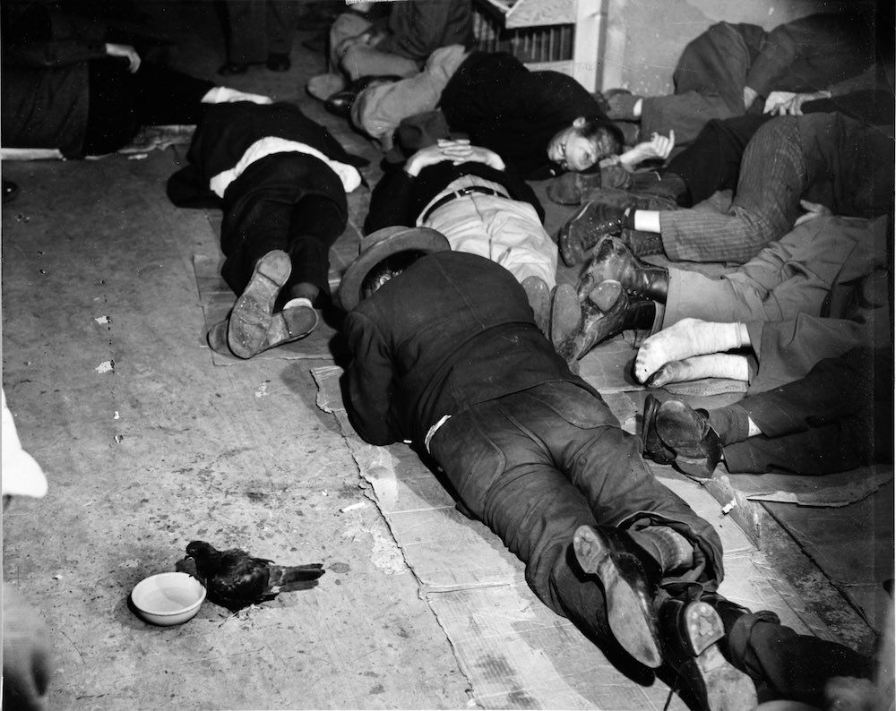 Jan. 1, 1942 A group of men sleep off their hangovers, while a lone pigeon drinks from a bowl of water set down nearby. - by Weegee