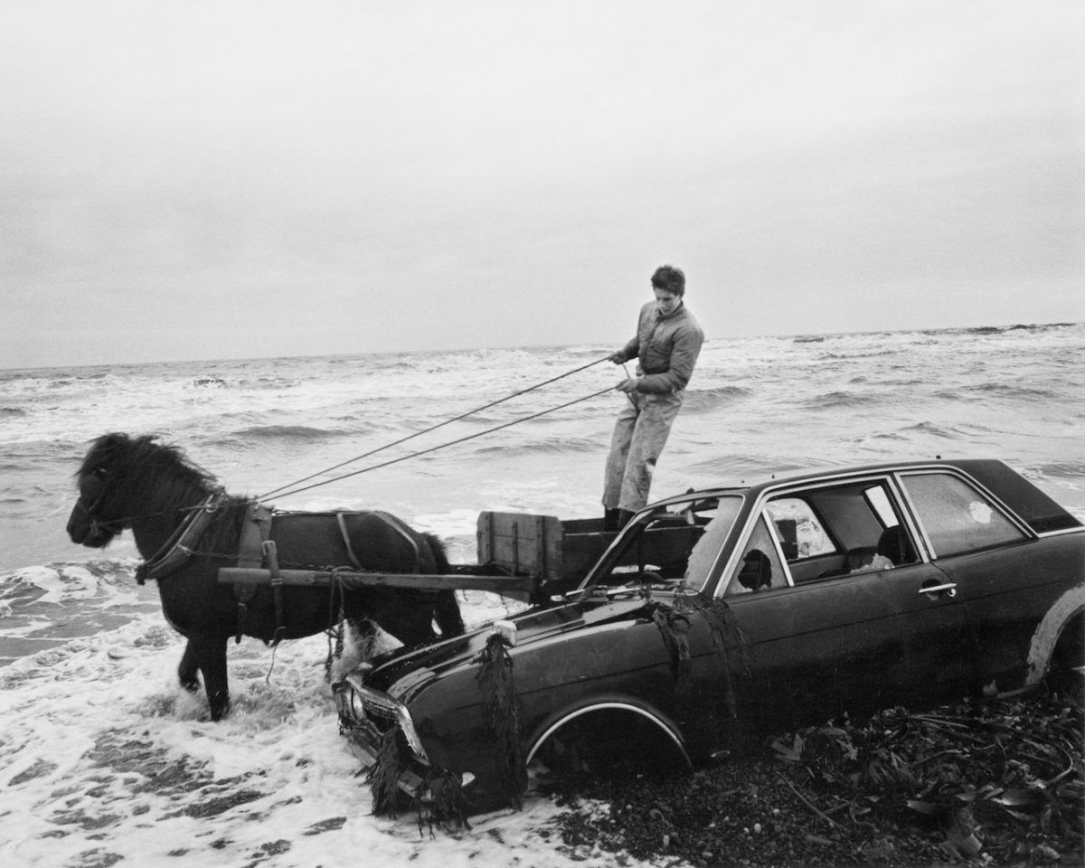 A Car Dumped on the Beach Has to Be Outmanoeuvred by the Seacoalers, Lynemouth, Northumberland, UK, 1982 © Chris Killip