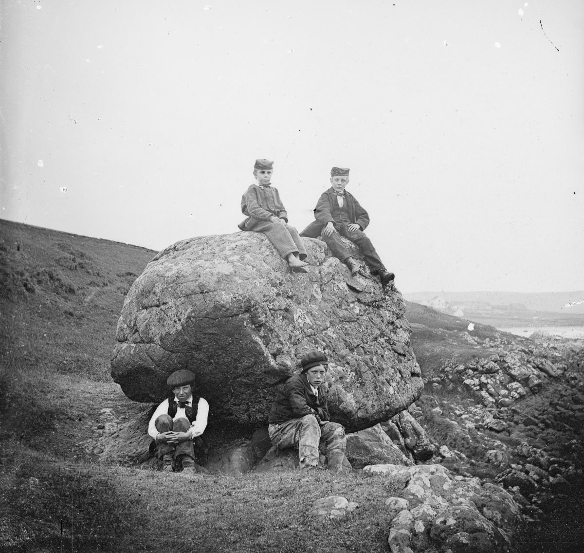 Four boys at the Rocking Stone at Islandmagee, County Antrim.1870