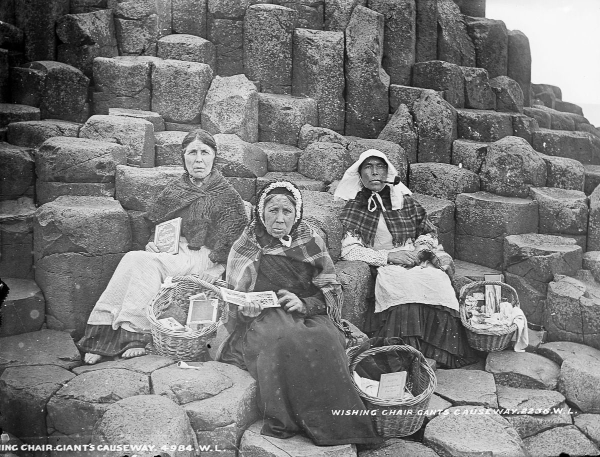 c. 1900 Women sell tourist trinkets and books on Fionn Mac Cumhaill's Wishing Chair at the Giant's Causeway, County Antrim.