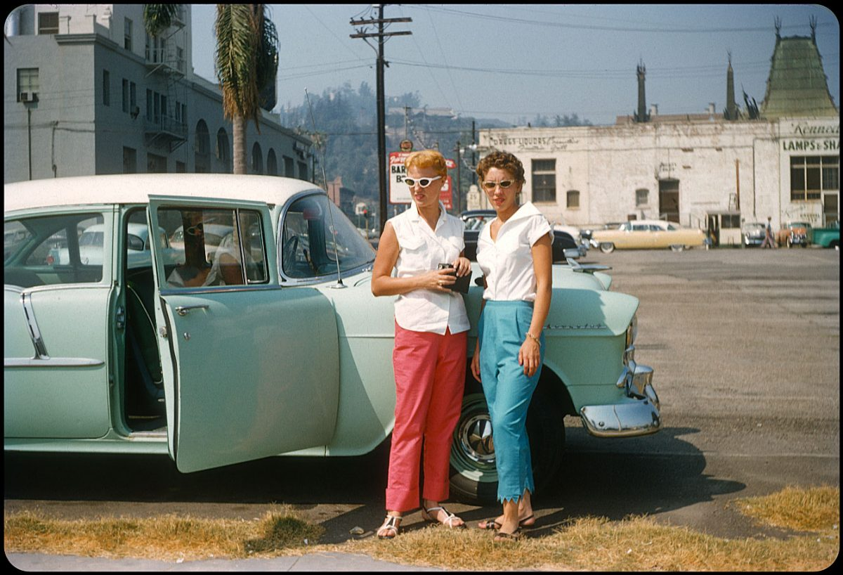 Hollywood! 1956 A couple of hip chicks from Illinois strike a pose behind the Hollywood Roosevelt Hotel and Grauman's Theater on N. Orange. The mint green 1955 Chevy 210 4-door sedan sets off the girls' red and blue slacks, and you almost miss the zig-zag alteration on miss blue-pants. She looks like trouble...