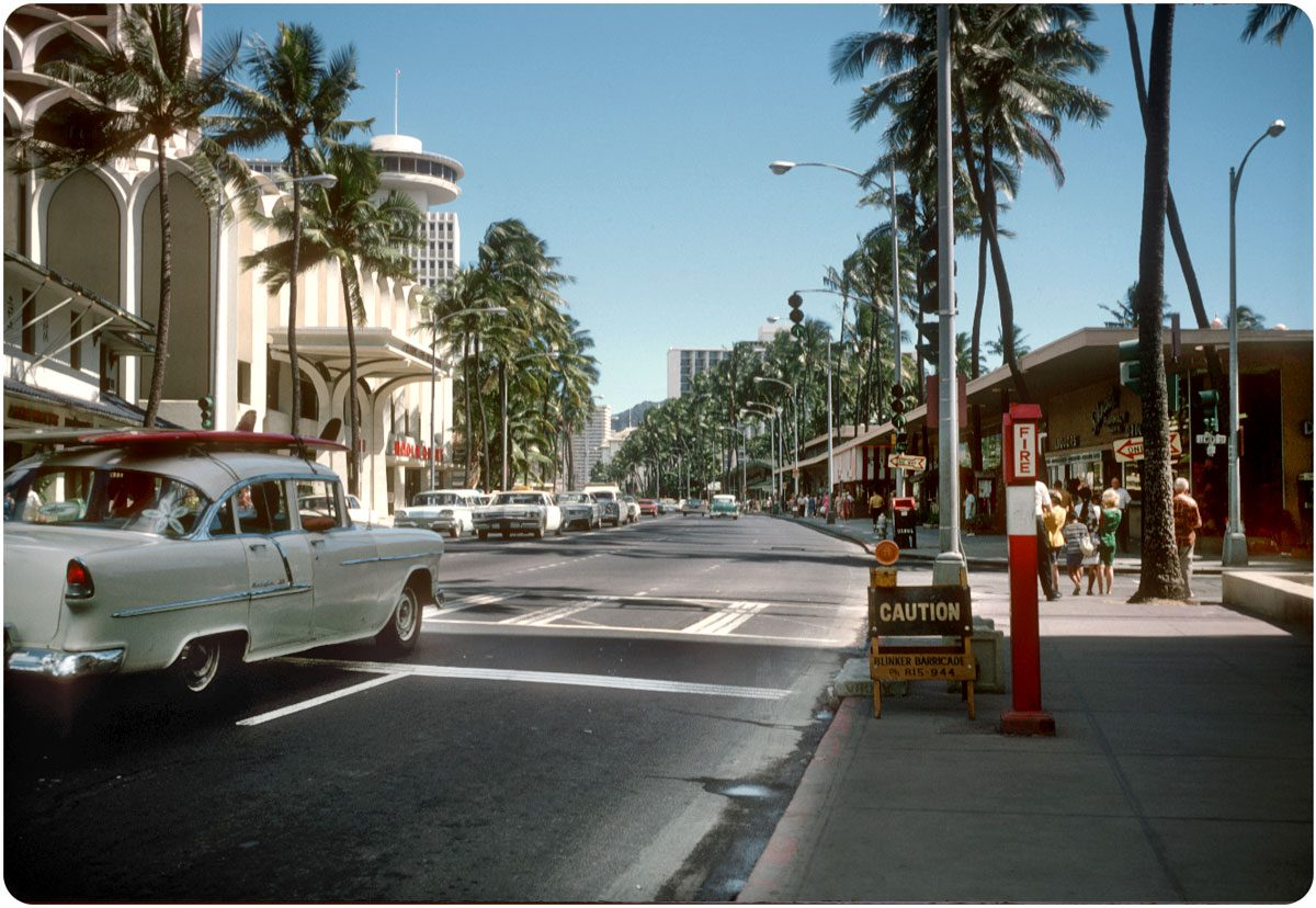 "Kalakaua Ave., Honolulu, Hawaii, 1967 A cream 1955 Chevy Bel Air with surfboards in tow is braking as it crosses Lewers St. on a green arrow. The Ala Moana Building's ""Top of Waikiki"" rotating restaurant can be seen above and behind the distinctive Bank of Hawaii / Galleria tower."
