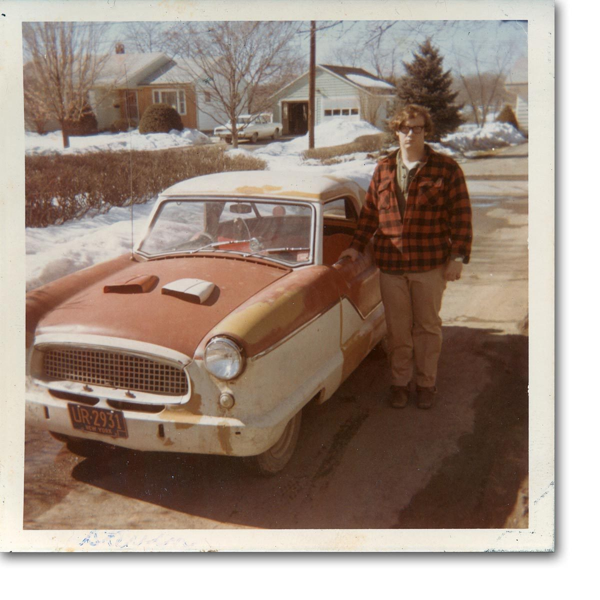 Steven Steven begrudgingly poses with his chick magnet, a Nash Metropolitan. (A Series III with air scoops?)