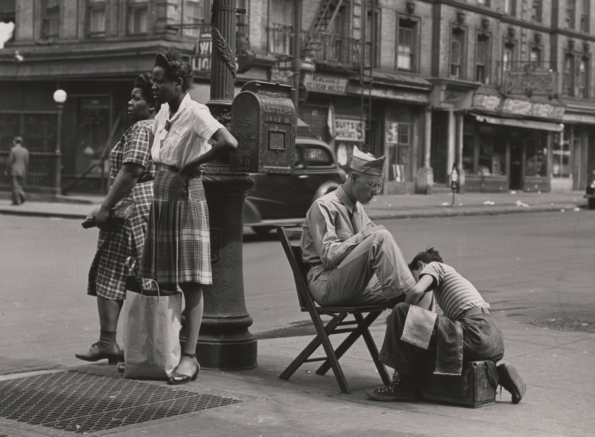 A soldier getting a shoe shine on 125th Street. 1946.