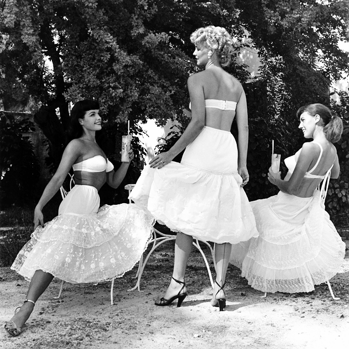 Miami, 1954– Bettie Page, Kathleen Stanley, and Bunny Yeager. Photographer Bunny Yeager was assigned to do some catalog photos of a line of petticoats and one of the models didn't show up. Bunny jumped in, taking off her clothes and putting on a petticoat, and took this shot using a self-timer on her camera.