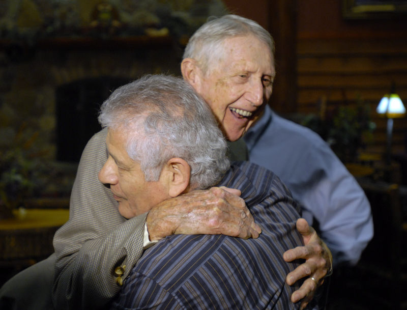 World War II infantry veteran Carrol Walsh, top, hugs Holocaust survivor Paul Arato