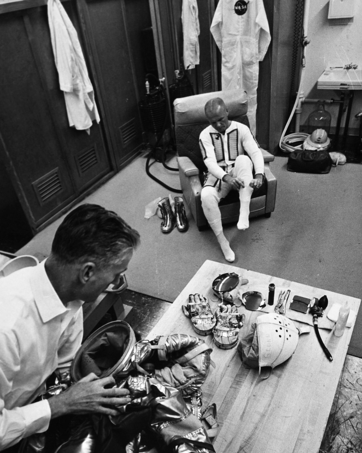 John Glenn (1921-2016). American Astronaut And Politician. Glenn And Space Flight Equipment Specialist Joe Schmitt Performing Suiting-Up Preparations Before The Launch Of Mercury Atlas 6 From Cape Canaveral, Florida, 20 February 1962.