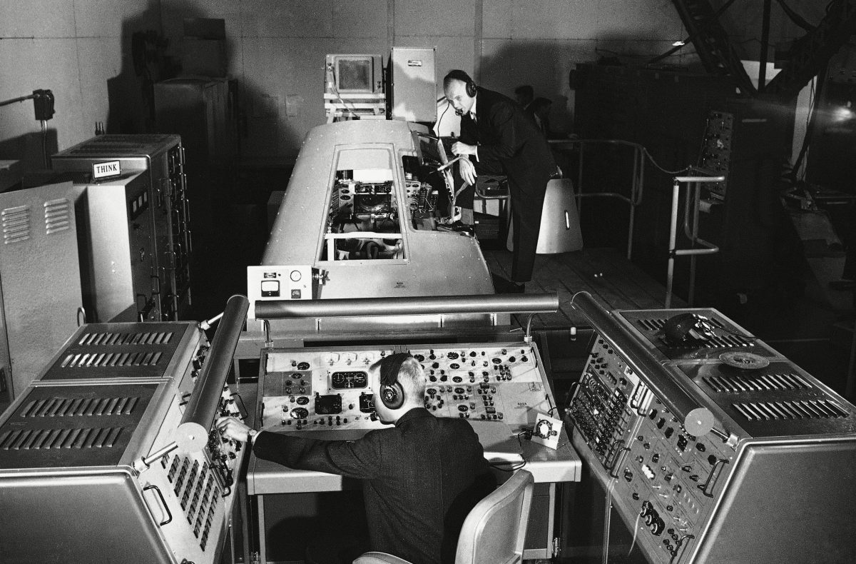 Marine Lt. Col. John Glenn, background, one of seven U.S. Astronauts, pose beside a Mercury Capsule procedure trainer with research engineer Charles Olasky at the control panel, Langley Field, Va. The controls simulate emergencies inside the capsule of the types which might be encountered during the first flight through space. The equipment is part of that used to train the astronauts at the NASA Research Center John Glenn Mercury Capsule 1961