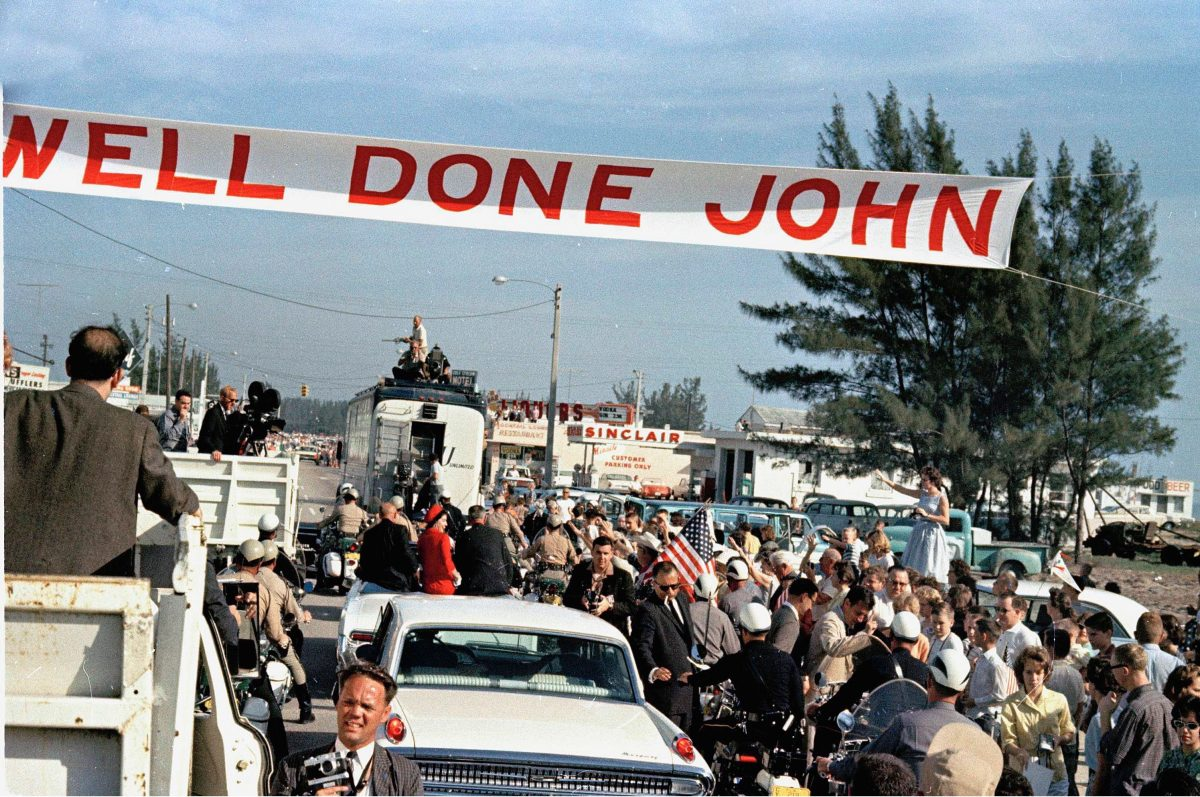 "Astronaut John Glenn, left, sitting on back of car, is greeted by admirers as his car passes under a ""Well Done John"" banner in Cocoa Beach, Fla., . Glenn's wife Annie, center, dressed in red, and Vice President Lyndon Johnson are in the car with him"