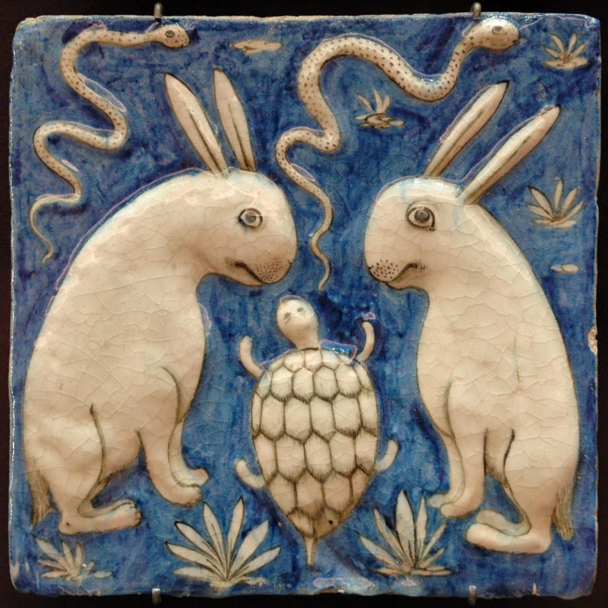 Tile with two rabbits, two snakes and a tortoise, illustration for thirteenth-century Marvels of Things Created and Miraculous Aspects of Things Existing byZakariya al-Qazwini, earthenware, moulded and underglaze-painted decoration, Iran, nineteenth century (Musée du Louvre, Paris)