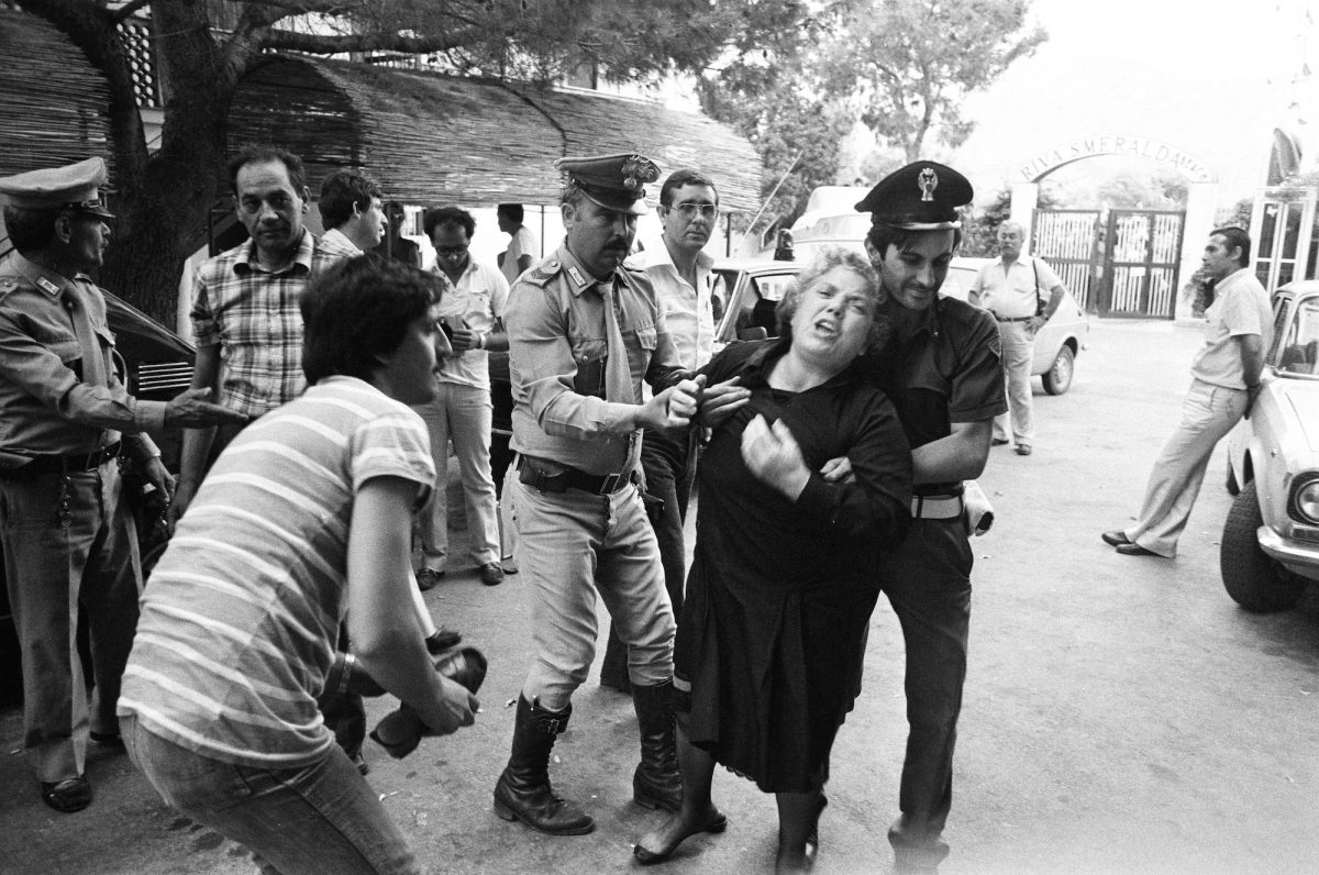 Woman shouts as police hold her back mafia Sicily Italy