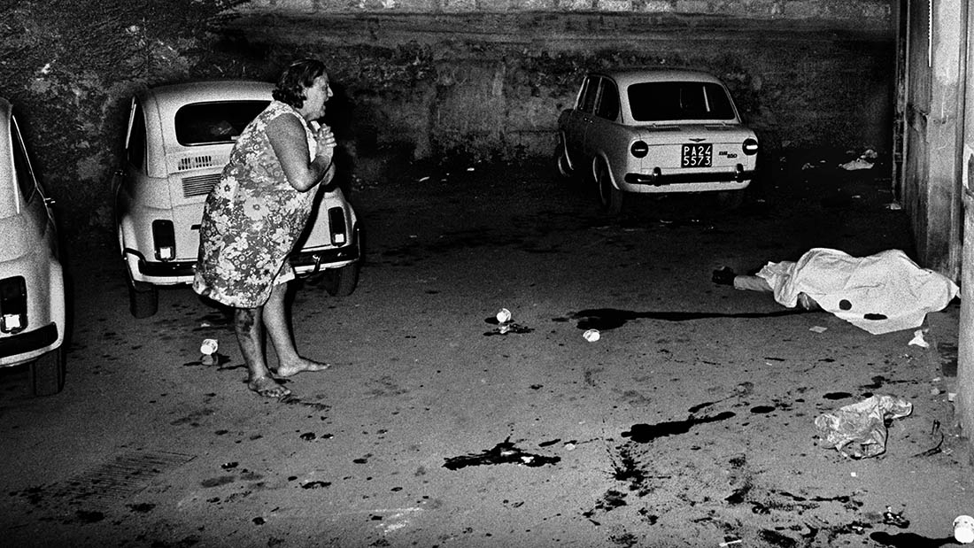 A woman screams near a dead body in a car park mafia Sicily Italy