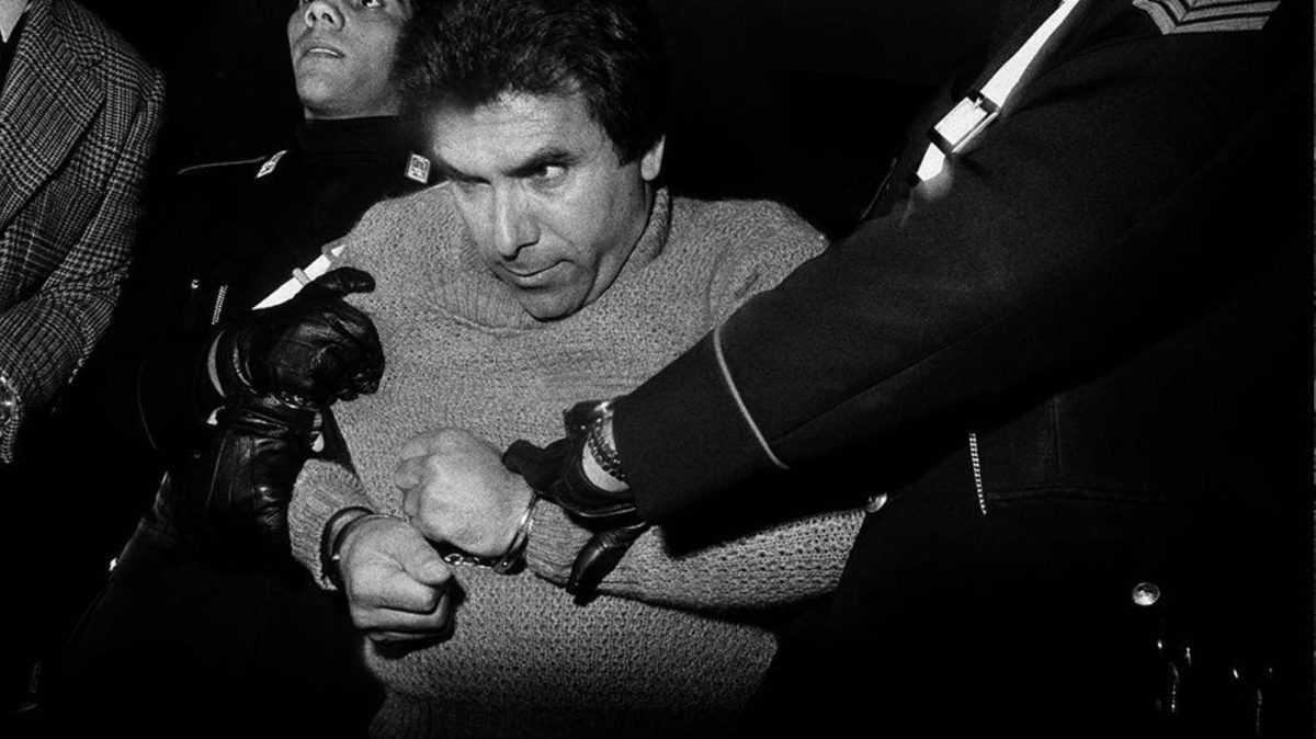A man in handcuffs struggles as police hold him mafia Sicily Italy