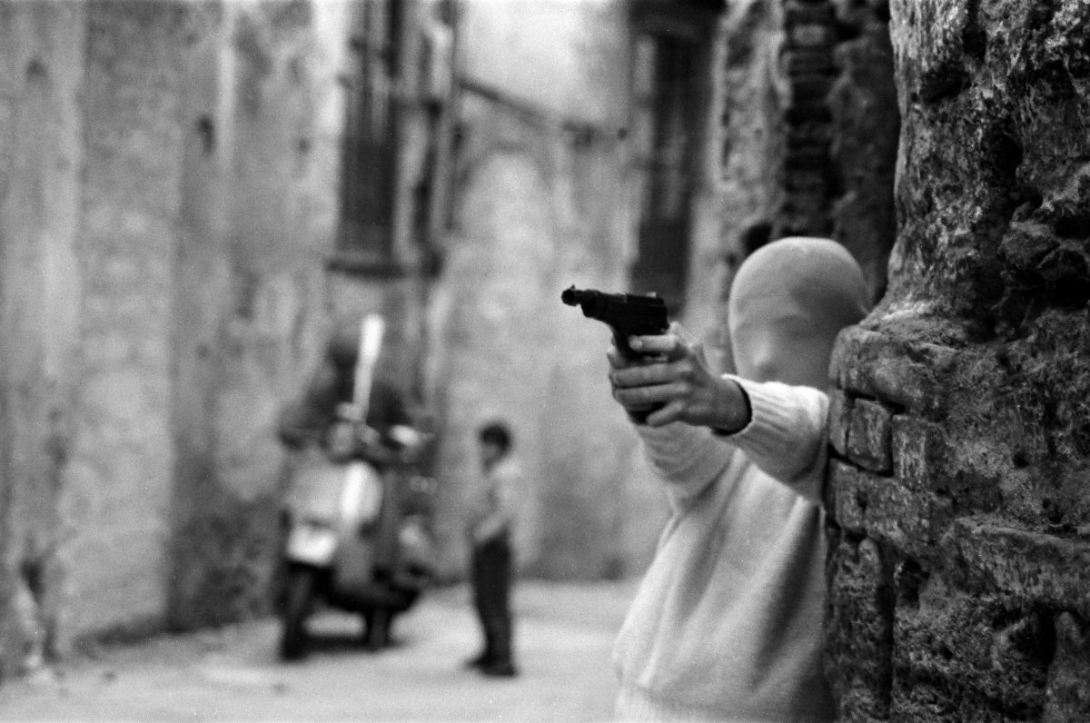 A boy in a stocking mask points a pistol mafia Sicily Italy