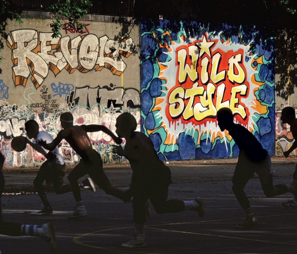 Men running on basketball court in front of colorful graffiti