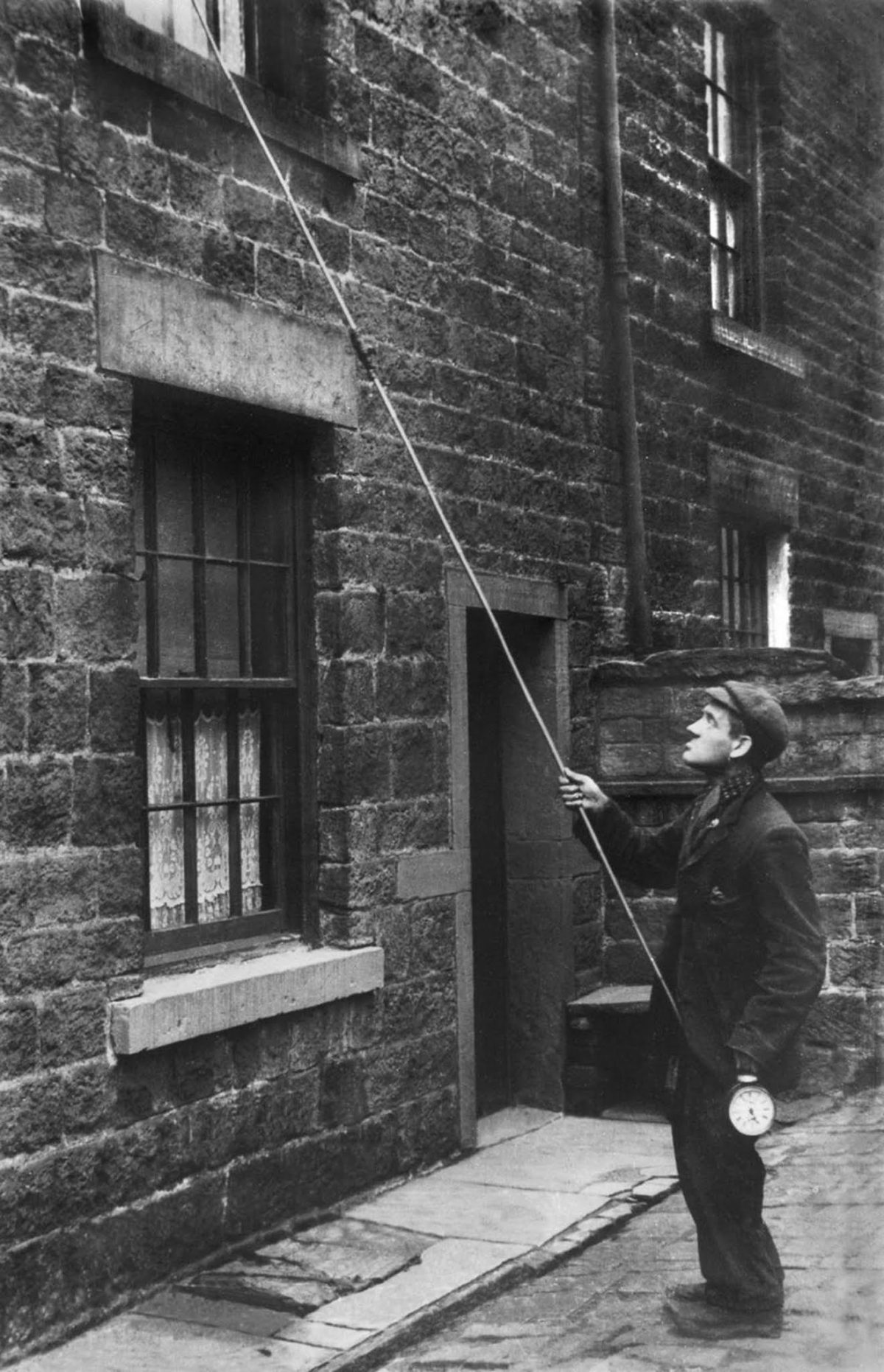 Young man taps on a second-floor window with a long pole