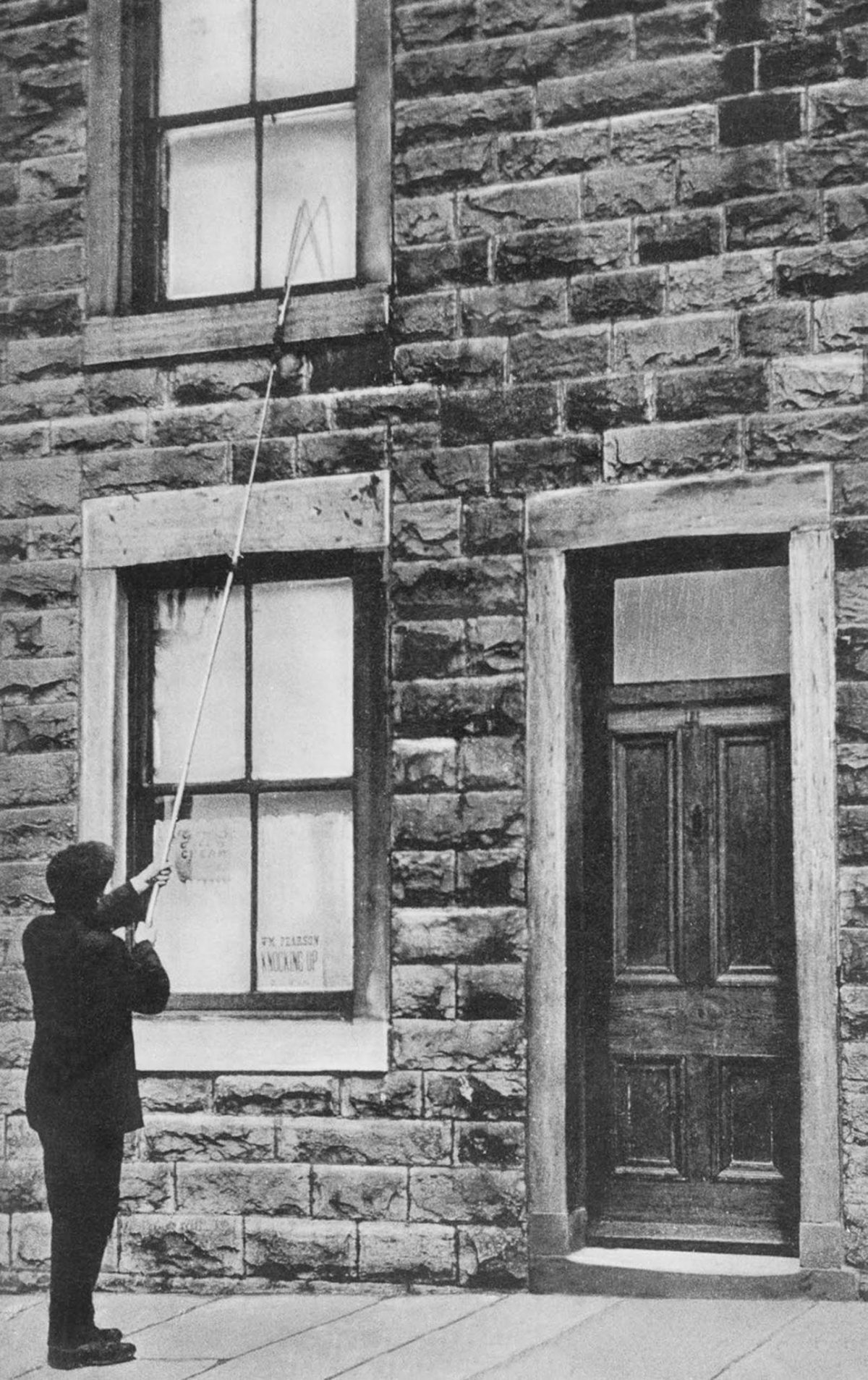 A man taps on a second-floor window with a long pole