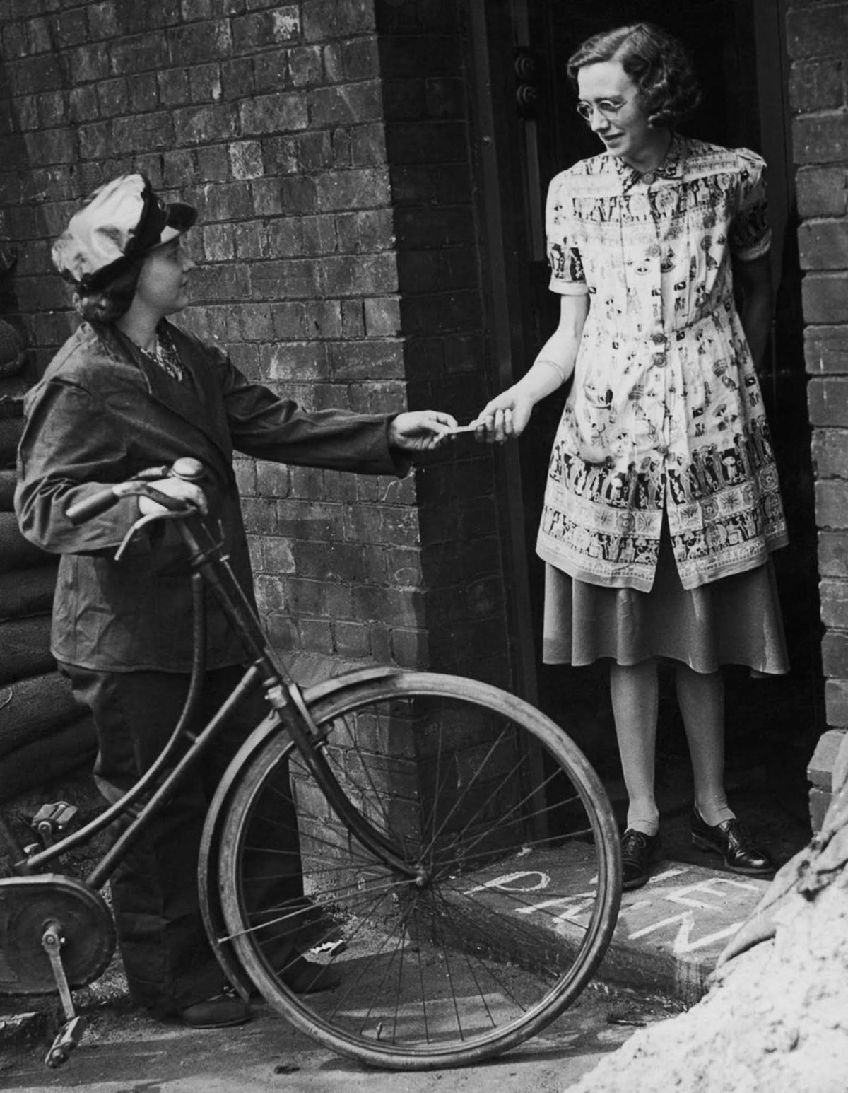 A woman on a bicycle hands another woman a message
