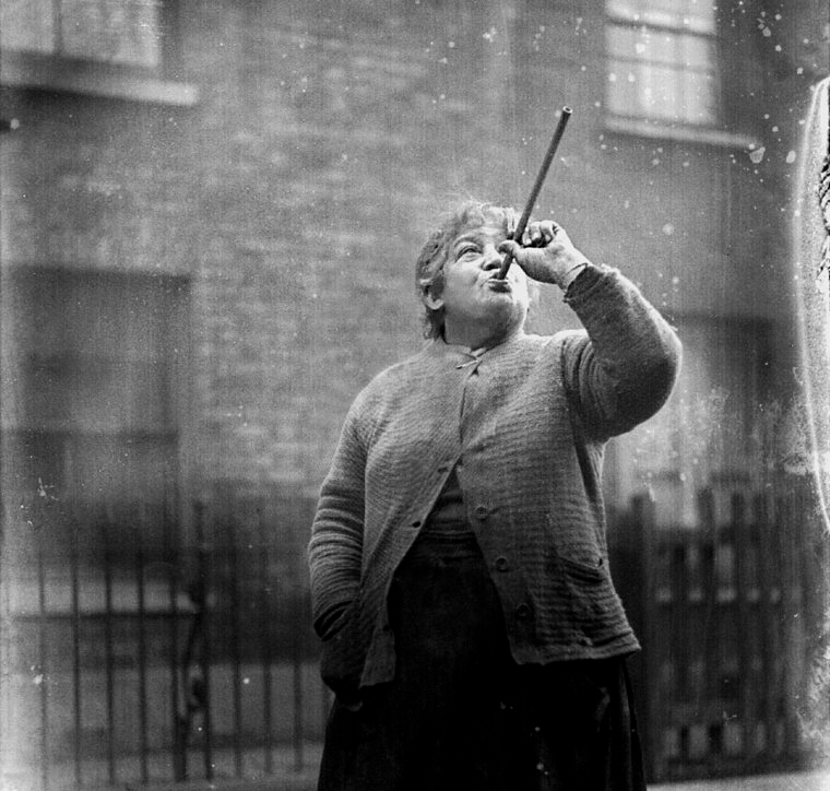 Woman points pea shooter at a window