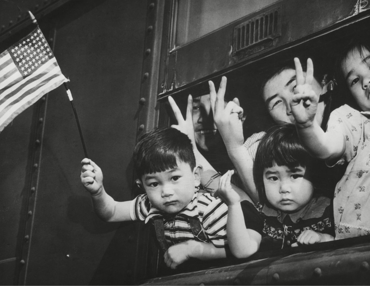 Japanese-American children waving from a train window as it leaves Seattle to take them to an internment camp for the duration of World War II. March 1942.