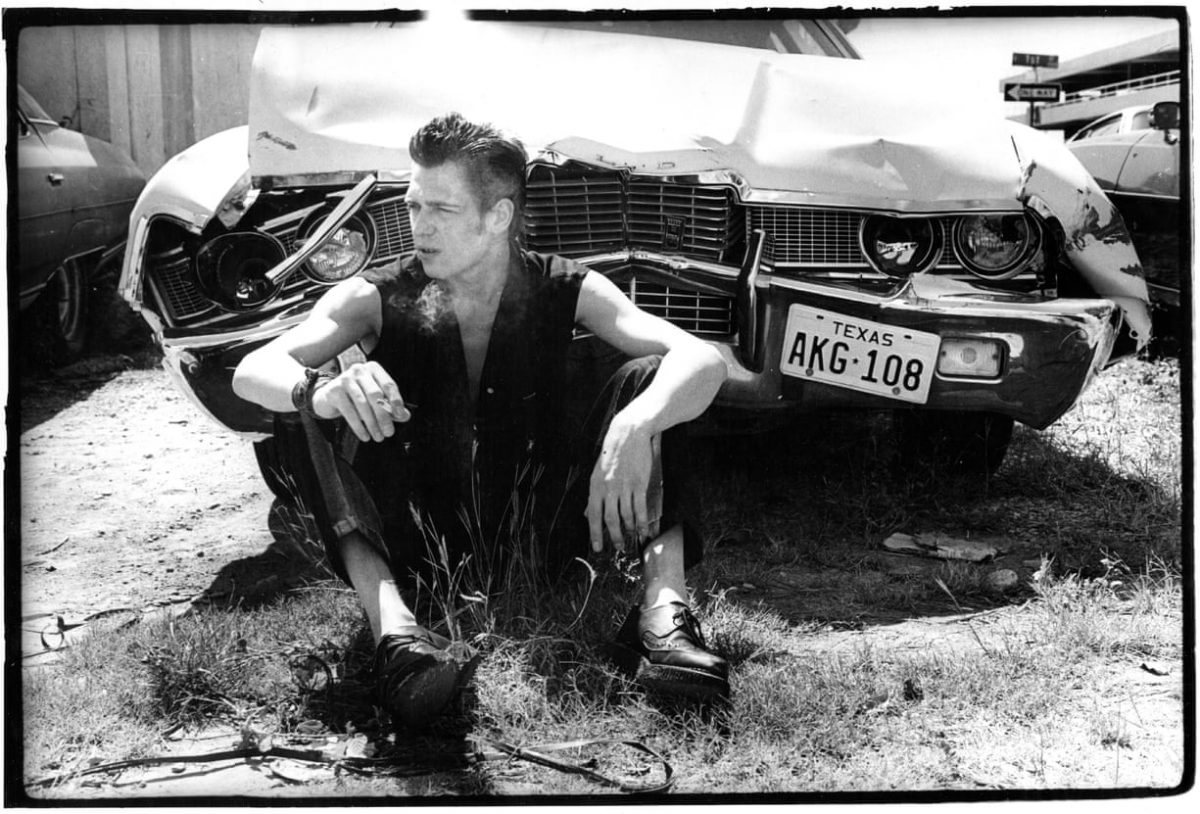 Paul Simenon smoking in front of a wrecked car with Texas license plates