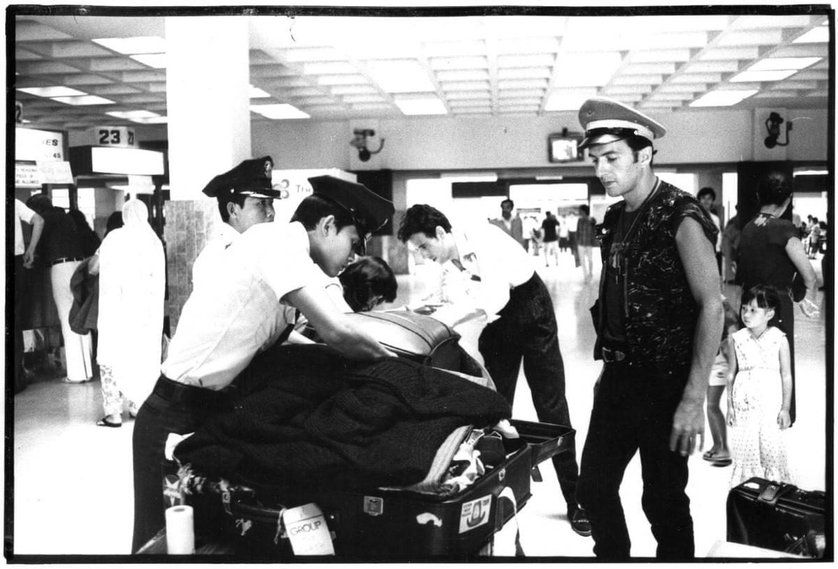 Joe Strummer stands at an airport while customs agents search his bags