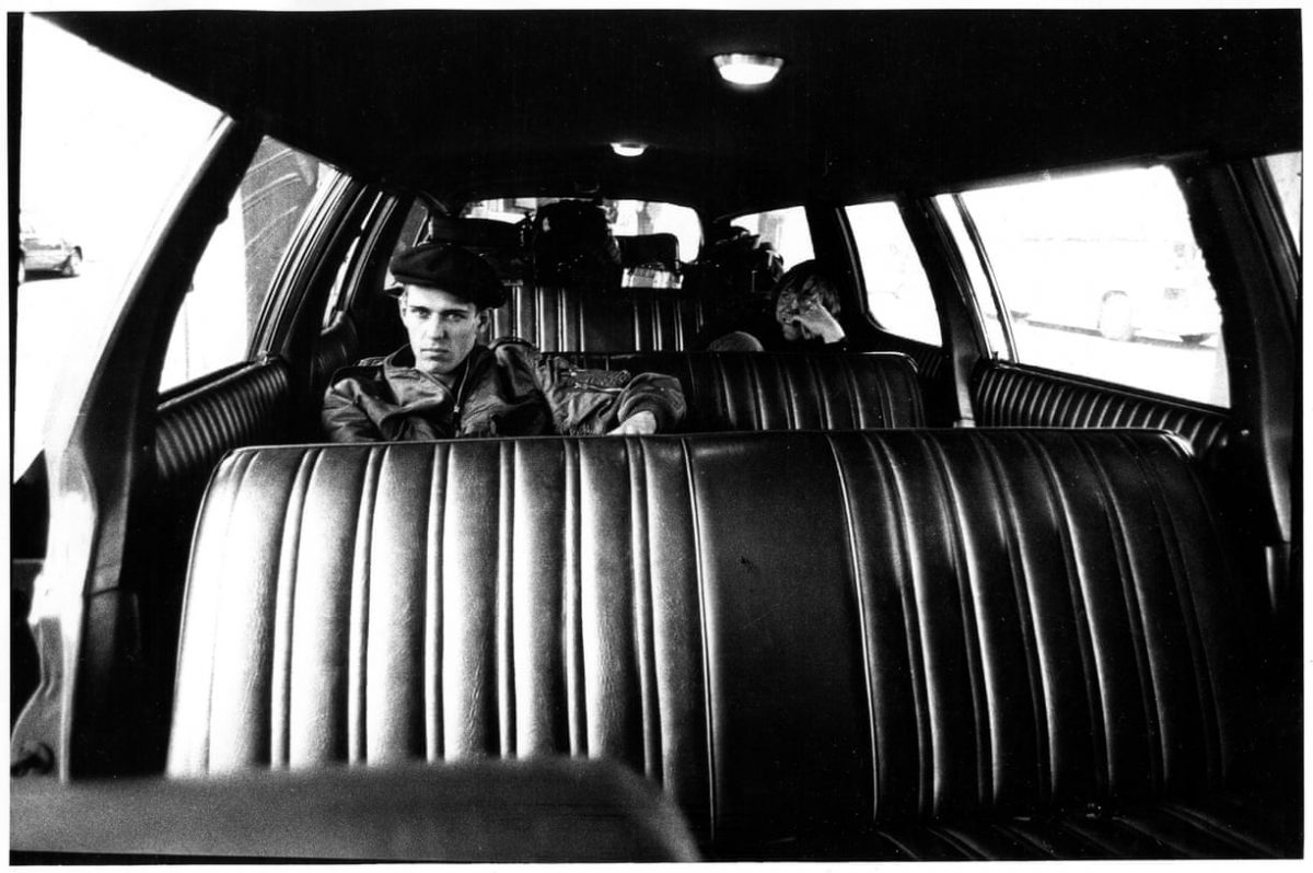 Paul Simenon sits, scowling, in the backseat of a tour van