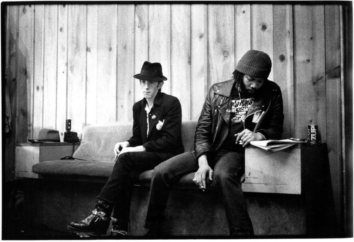 Clash drummer Topper Season on a bench next to an unidentified man