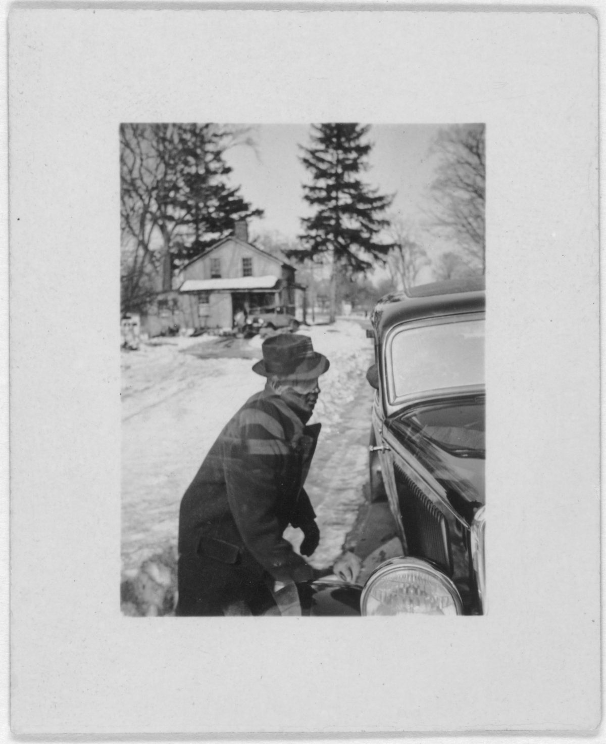 Leadbelly, three-quarter-length, profile, facing right, lifting car out of snow, at the home of Mary Elizabeth Barnicle, Wilton, Conn
