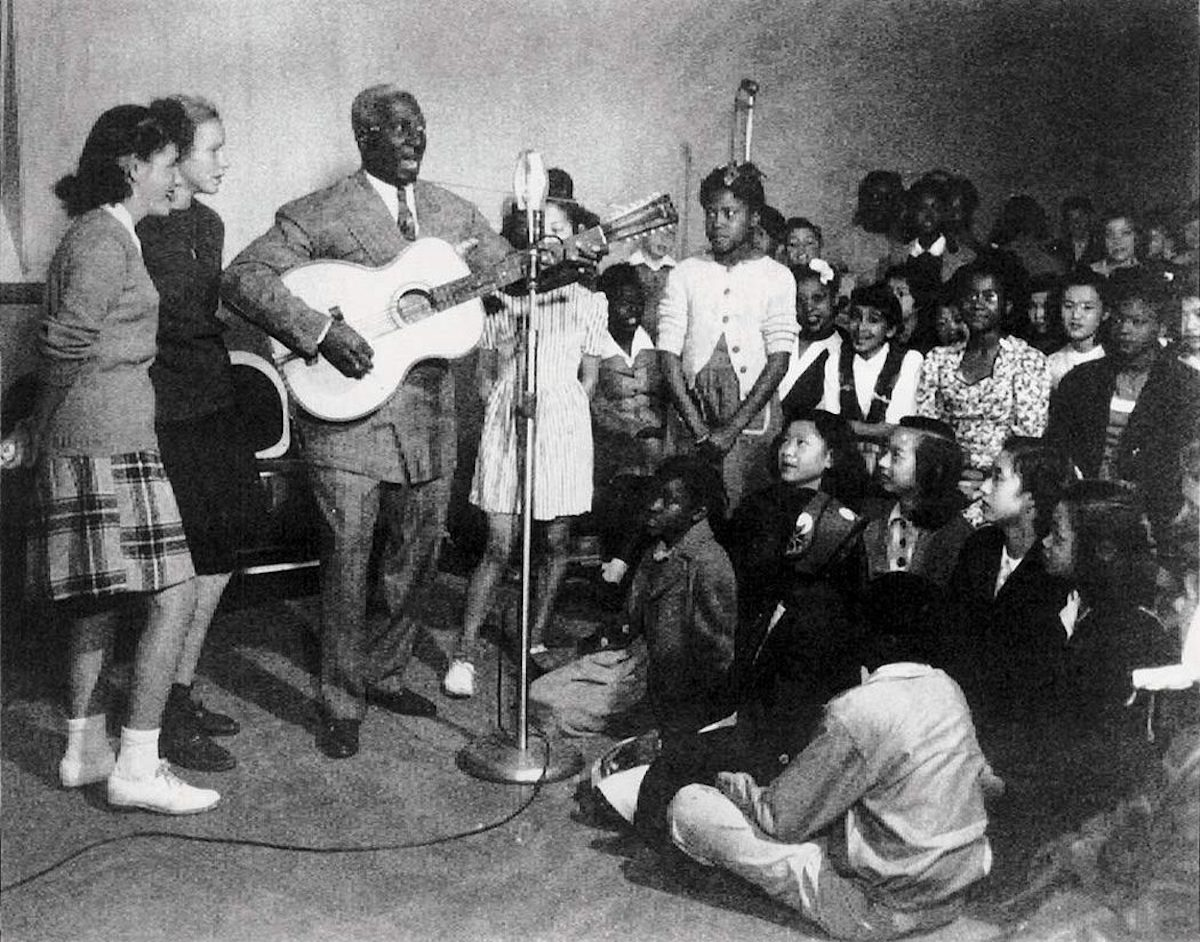 Lead Belly performs for a group of children