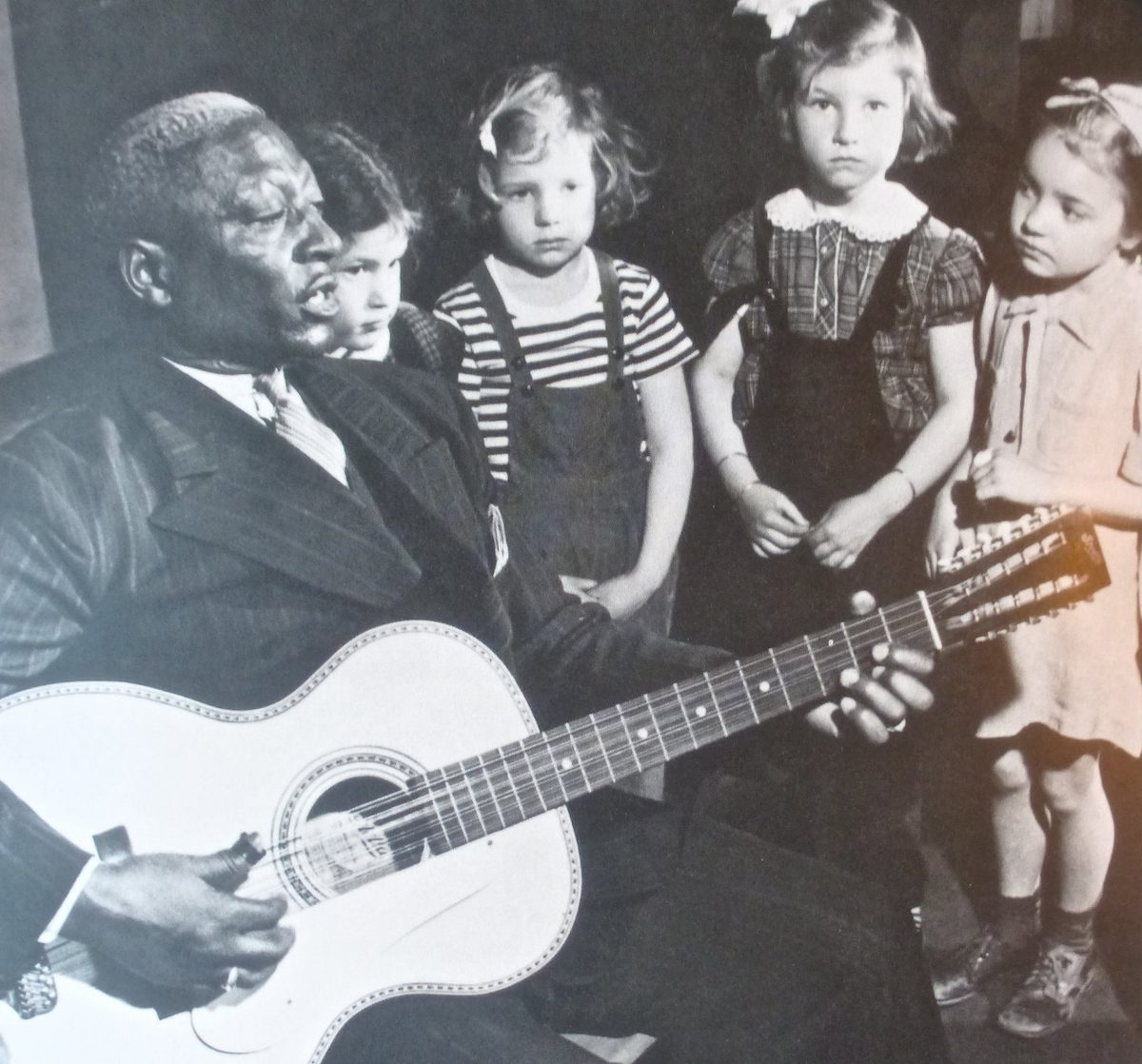 Lead Belly plays for a group of children
