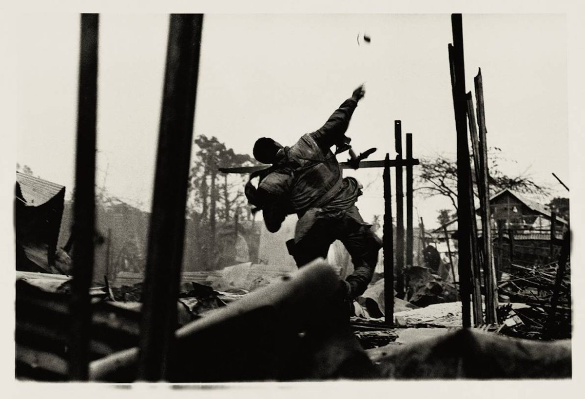 "Don McCullin, ""US soldier as he throws a grenade at North Vietnamese soldiers, moments before he was shot by a sniper,"" Hue, Vietnam, 1968"