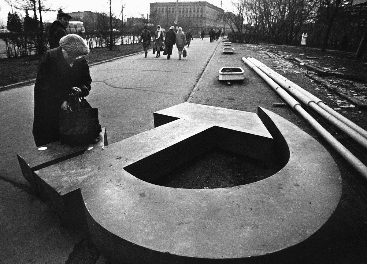 A woman reaches into her bag, which rests on a fallen Soviet hammer-and-sickle on a Moscow street in 1991