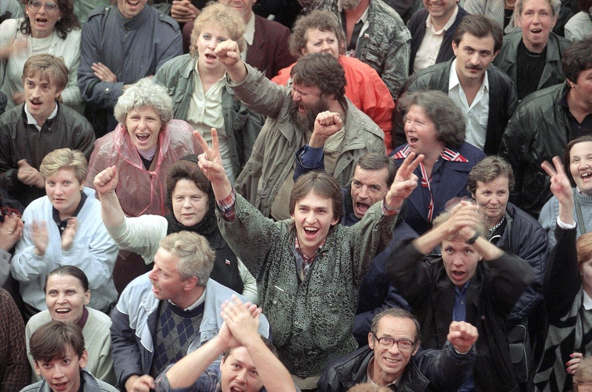 Part of a large crowd, outside the Russian Parliament building in Moscow, celebrates the news that the hardline Communist coup has failed, on August 22, 1991