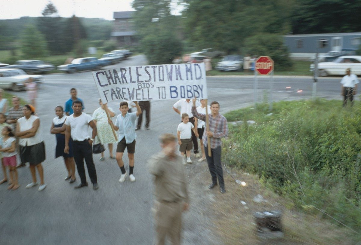 A sign is held up as the funeral train passes through Charlestown, Maryland, on June 8, 1968