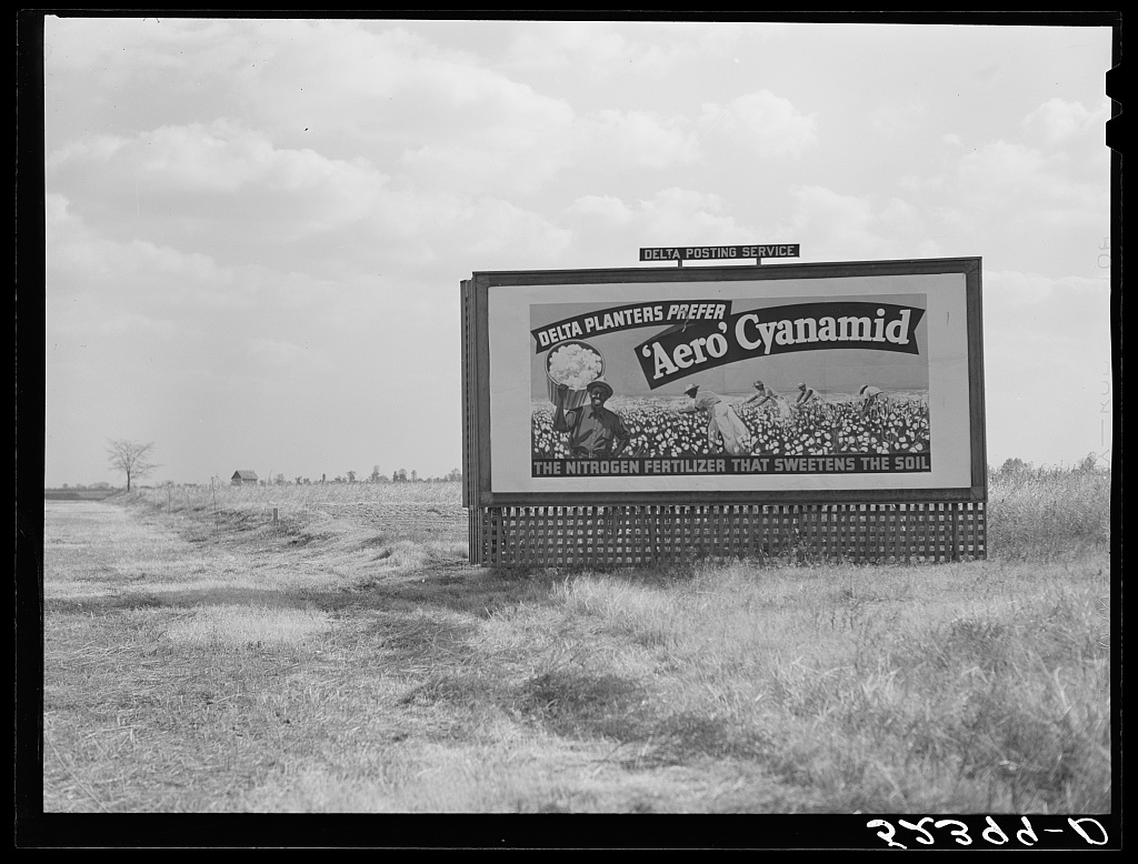 Billboard advertising fertilizer dusted over the cotton fields by aeroplanes. Mississippi Delta Contributor Names Wolcott, Marion Post, 1910-1990, photographer Created / Published 1939 Oct.