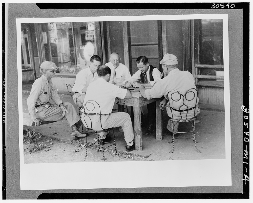 Playing dominoes or cards in front of drug store in center of town in Mississippi Delta, Mississippi - October 1939