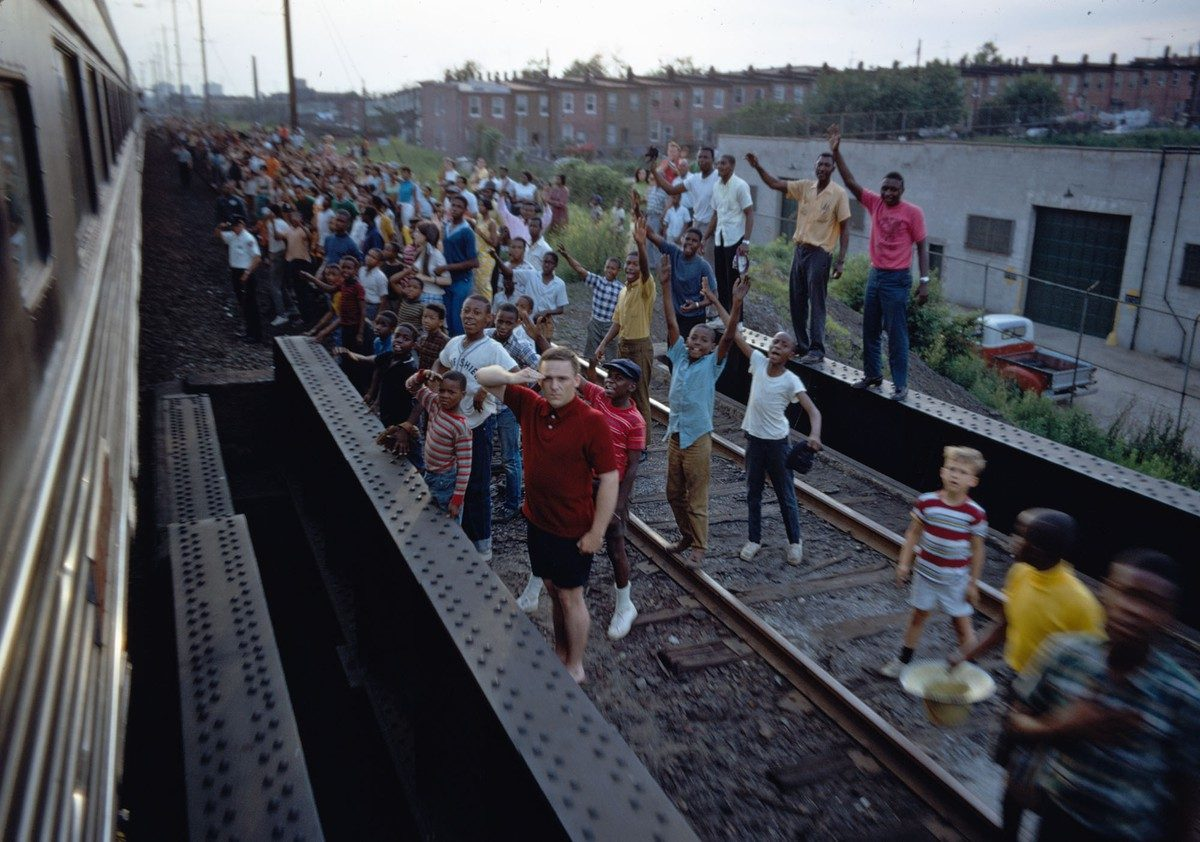 People wave and salute as Robert F. Kennedy's funeral train travels past, rolling from New York City to Washington, D.C., on June 8, 1968