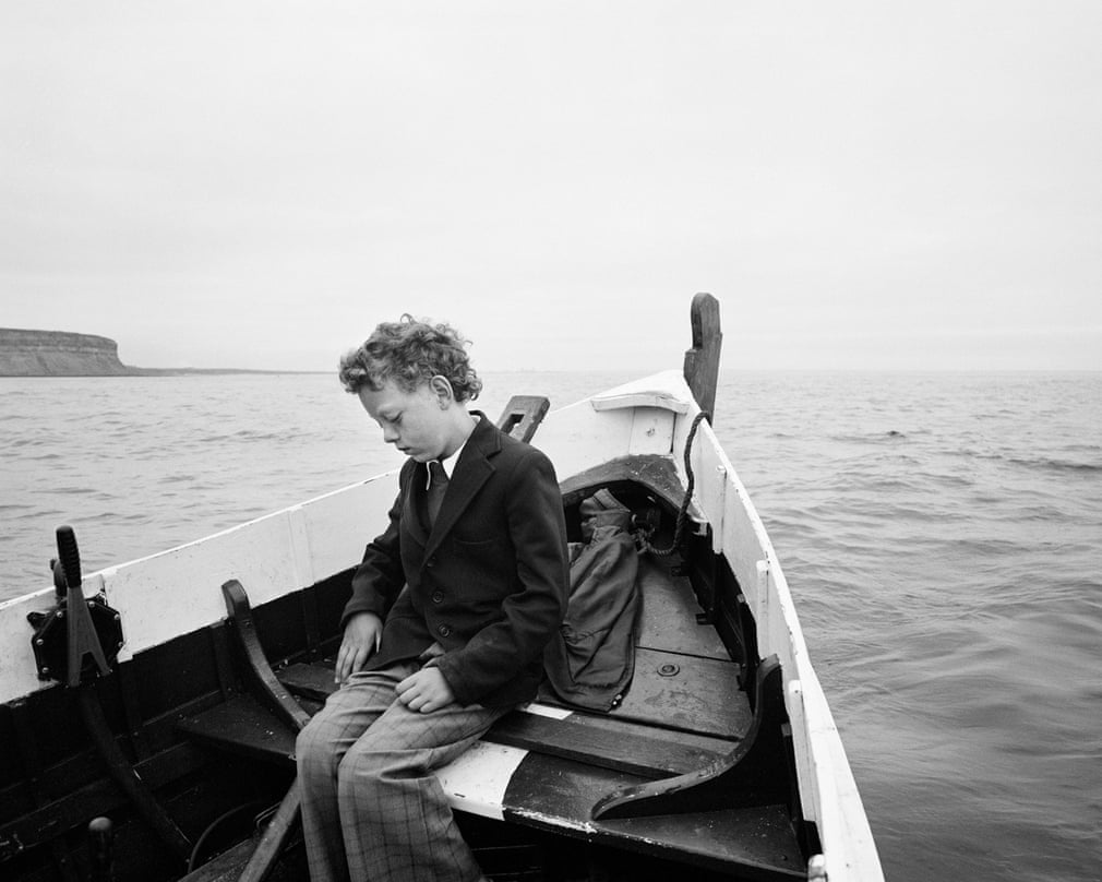 Simon being taken to sea for the first time since his father drowned, Skinningrove, North Yorkshire, 1983 Photograph- Photograph by Chris Killip