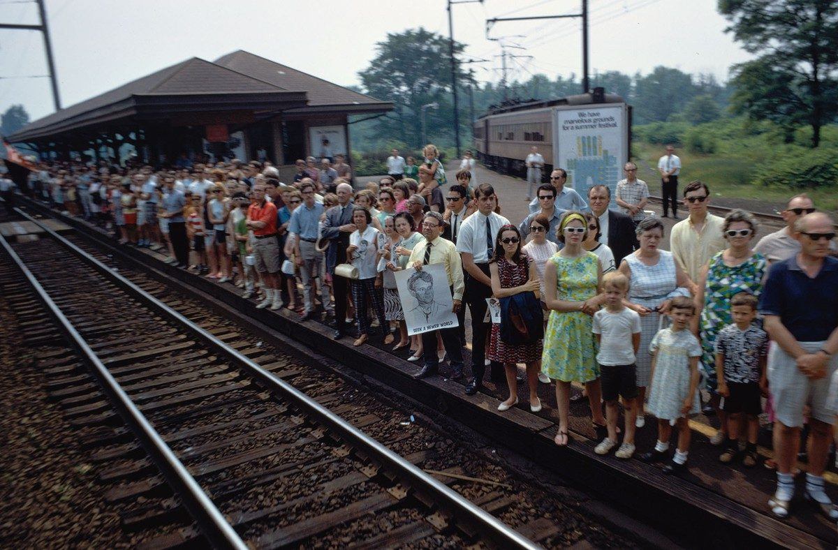 The funeral train rolls through Princeton Junction, New Jersey, on June 8, 1968. Several people hold portraits of Robert F. Kennedy, including a man whose poster reads Seek a Newer World.