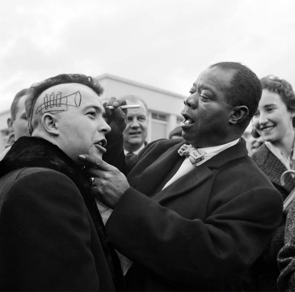 Louis Armstrong drawing a trumpet and autographing the side of a young man's head in Nice, France]