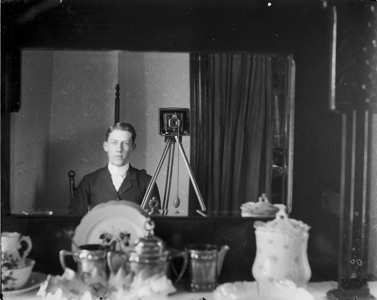 Portrait of man reflected in mirror with camera and cable releaseGeorge Silas Duntley Photographs 1899-1918