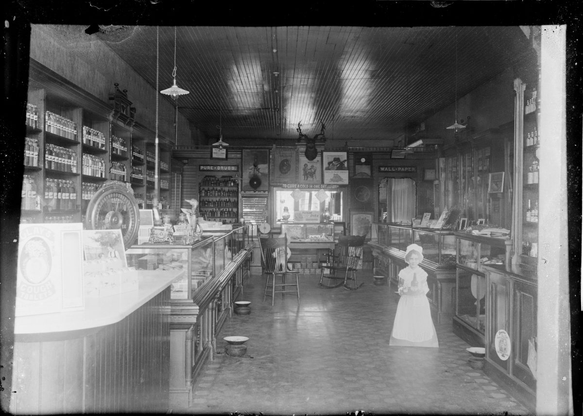 Shop with signs that read - Pure Drugs. To Cure A Cold In One Day. Wall PaperGeorge Silas Duntley Photographs 1899-1918